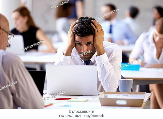 Stressed Businessman Working On Laptop In Busy Office