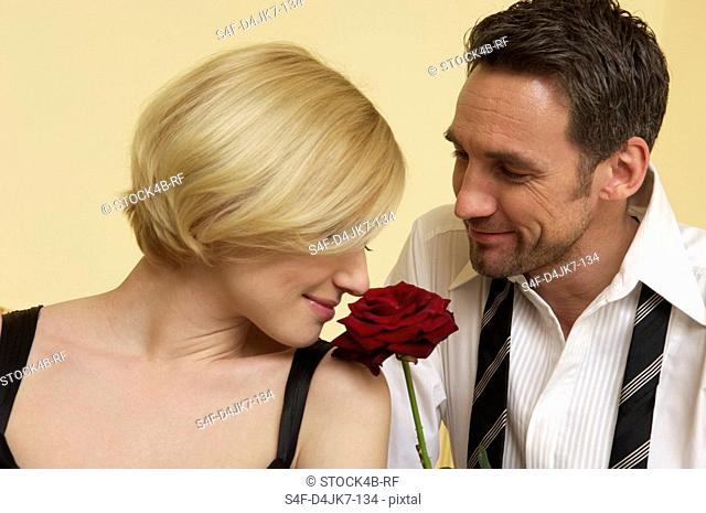Close-up of couple, woman smelling a rose