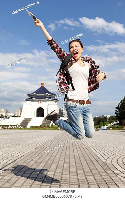 Young woman jumping in mid-air and smiling happily