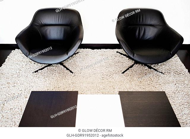 Two armchairs on a carpet