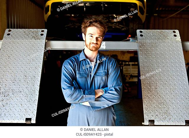 Portrait of male mechanic behind car lift in garage