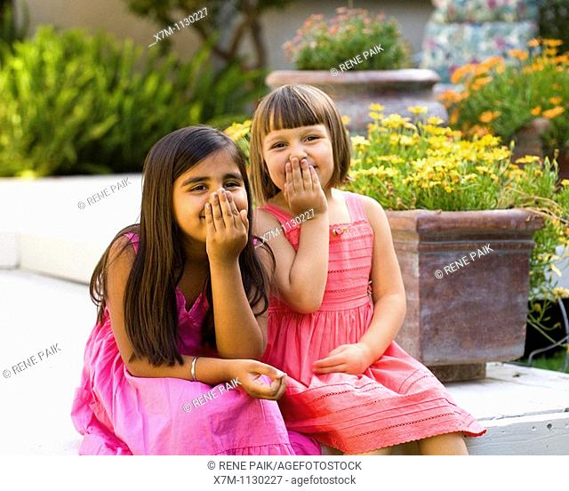 2 little girls, caucasian and Indian, talk and giggle on the porch