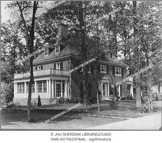 Landscape shot, large three-story brick house, with a side balcony, surrounded by trees with leaves, Roland Park/Guilford, United States, 1910