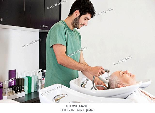 A male hairdresser washing a female clients hair