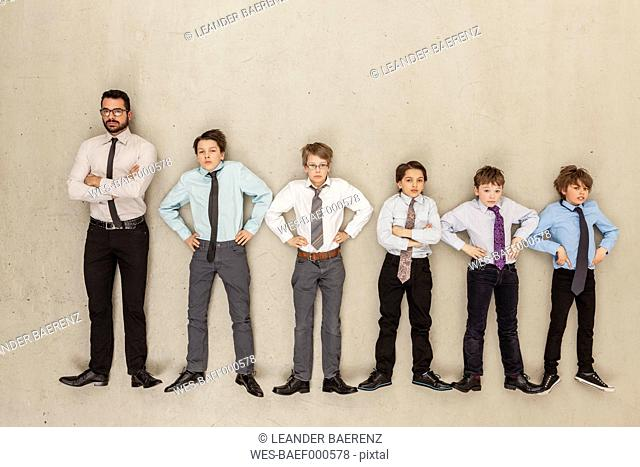 Businessman and boys standing in row