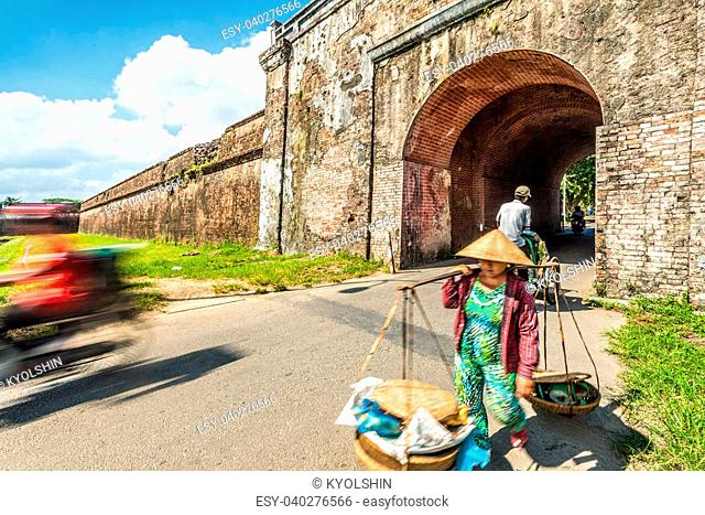 Asian woman in traditional conical hat carrying baskets at Hue city citadel gates in Vietnam, Asia. Ancient building, blue sky with clouds in background
