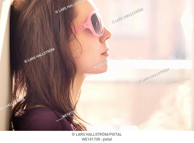 Woman with sunglasses. Side view portrait of young woman with cool attitude. She is sitting by a window in sunlight with a carefree relaxed expression