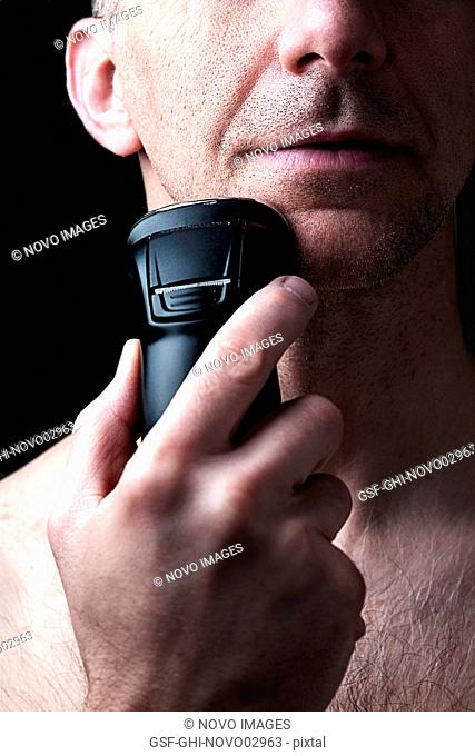 Man Shaving Face with Electric Razor Against Black Background