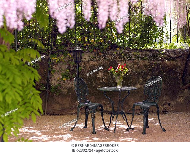 Still life, round, antique cast-iron garden table and two chairs, in a romantic courtyard