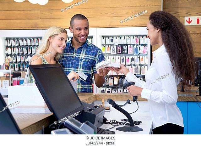Couple making a purchase from store assistant in shop