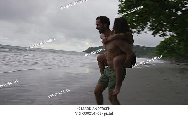 Wide panning slow motion shot of couple playing on beach / Manuel Antonio, Costa Rica