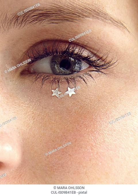 Close up of glitter stars under young woman's eye