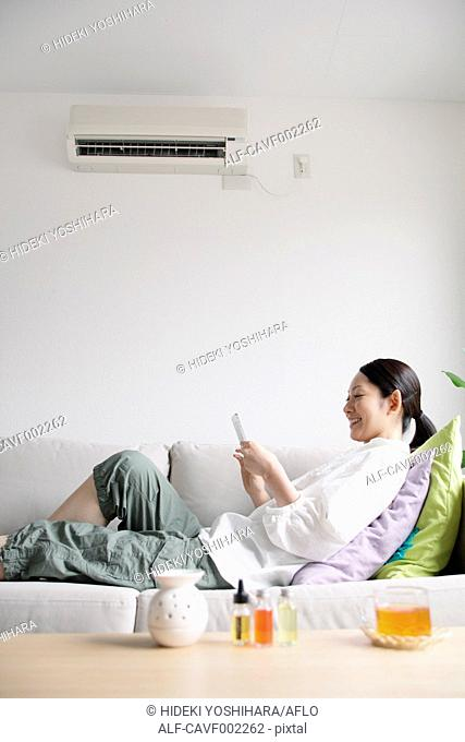 Woman using a Smartphone on the sofa