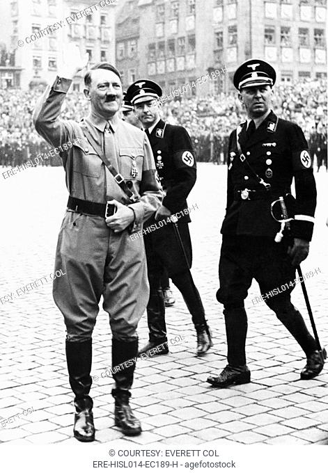 Adolf Hitler saluting, with two SS generals in uniform behind him, at Nazi Party Day, Nuremberg, Germany. 1937
