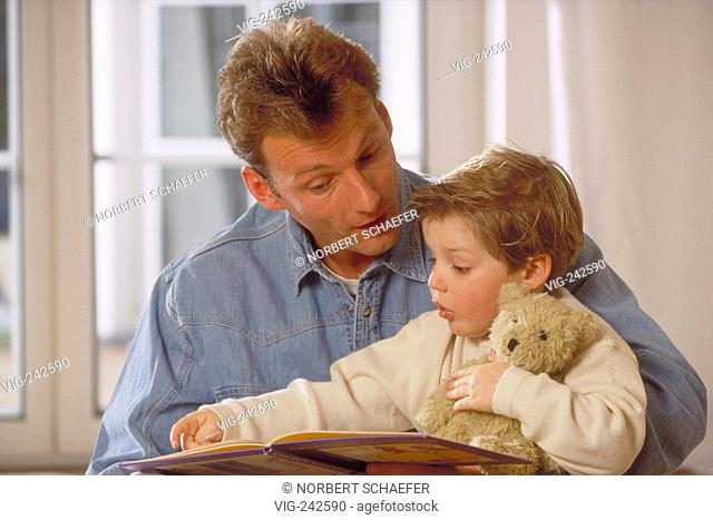 portrait, indoor, man wearing jeans shirt reads with his 4-year-old son on his knees holding his teddy a picture book  - GERMANY, 09/03/2005