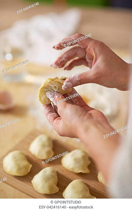 Woman closing dumpling with traditional filling