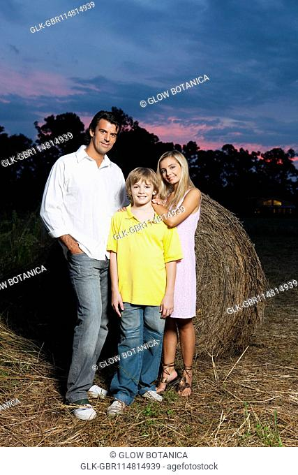 Portrait of a couple with their son in a field