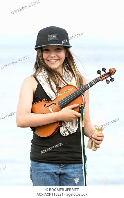 A young musician breaks for an ice cream cone treat during an impromptu outdoor ceilidh, Campbell River, Vancouver Island, British Columbia, Canada