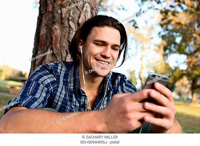Young man sitting by tree wearing earphones looking at smartphone smiling