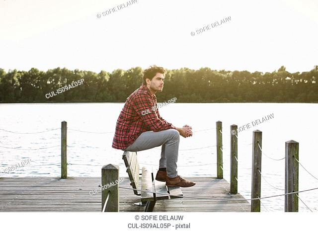 Young man sitting on bench on jetty looking across water