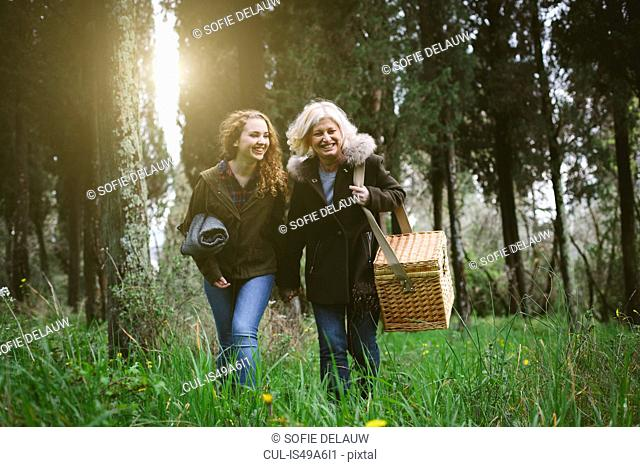 Mother and teenage daughter strolling with picnic basket