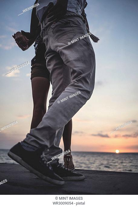Low angle shot of two people dancing on a sea wall in front of the ocean