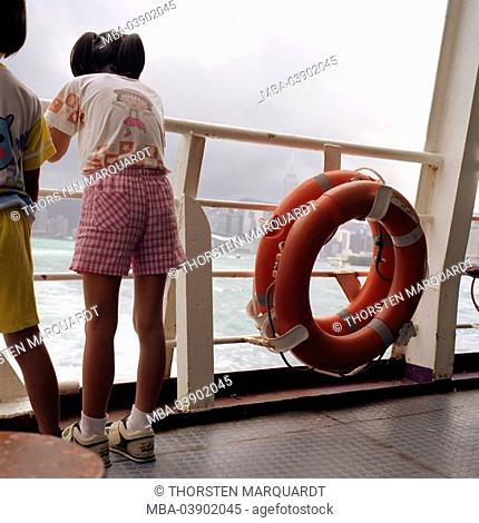 China, Hong Kong, ferry, rail, children, back view, ferryboat, ship, people, Asians, Chinese, girl, shorts, gym shoes, view, stands enjoys, gaze, city, shipping