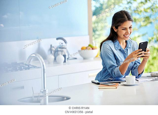 Smiling woman texting with cell phone at kitchen counter