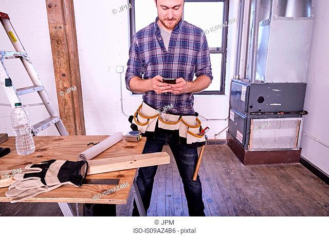 Carpenter in workshop texting on smartphone