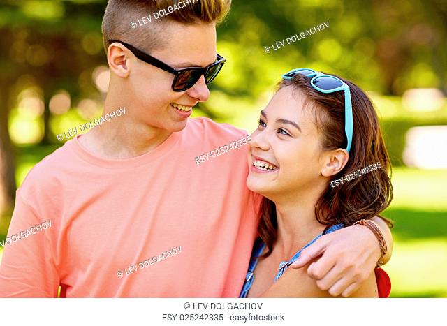 holidays, vacation, love and people concept - happy smiling teenage couple hugging and looking at each other at summer park
