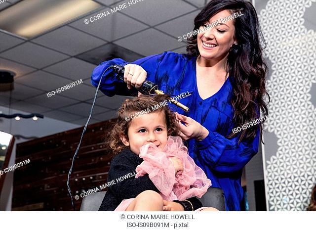Stylist curling girl's hair in salon
