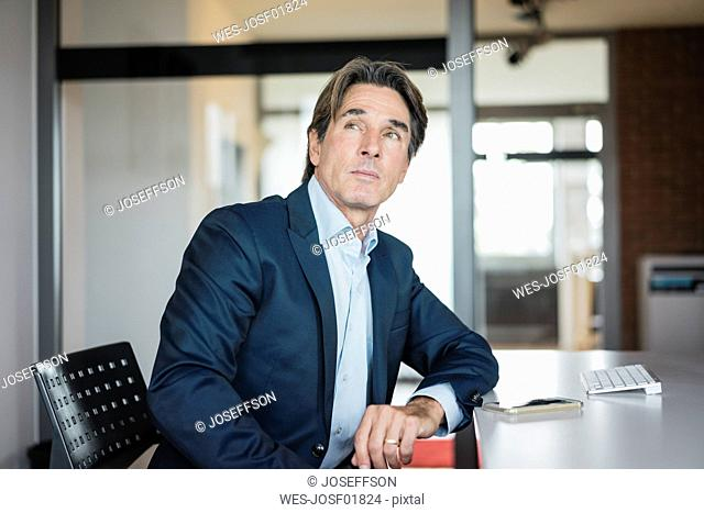 Businessman at desk in office thinking