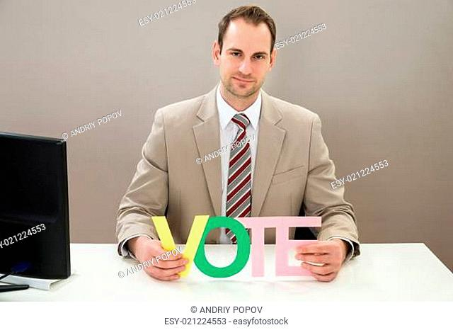 Mid Adult Businessman Holding The Multicolored Word Vote At Desk