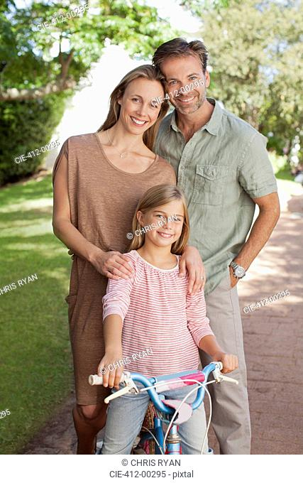 Portrait of smiling parents with daughter on bicycle