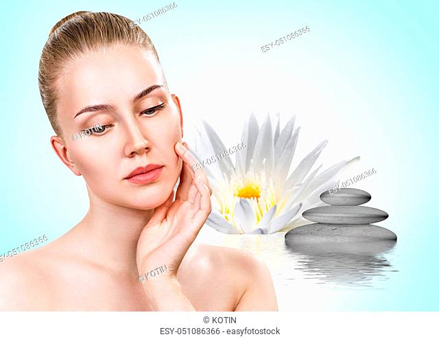 Beautiful woman in ripple water with lotus flower. Spa concept. Over blue background