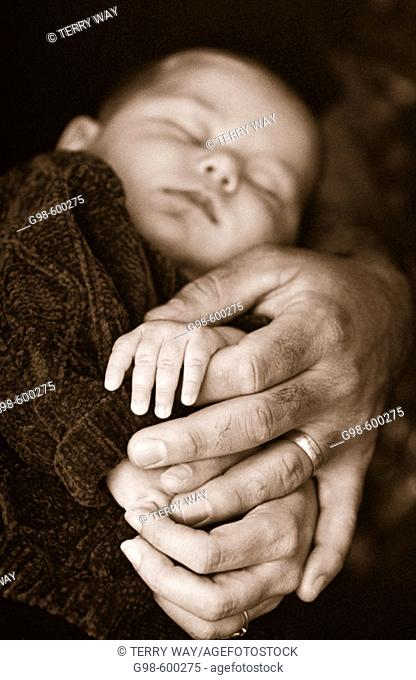 Baby with hands of parents in black and white
