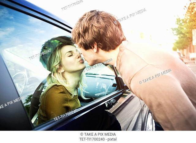 Young couple kissing through window of car