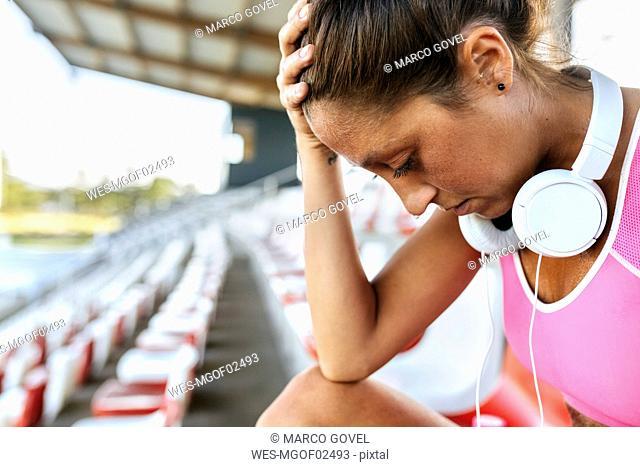 Female athlete with headphones looking down