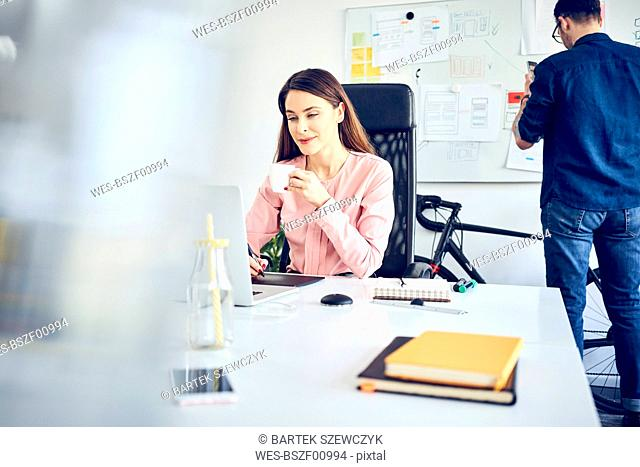Woman working at desk in office with colleague in background