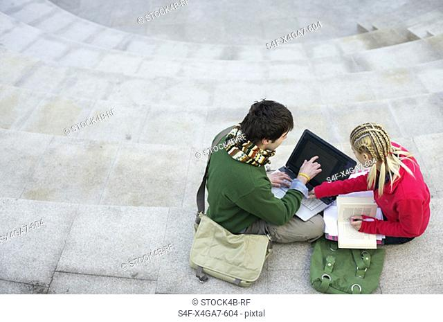 Young couple using a laptop on a staircase