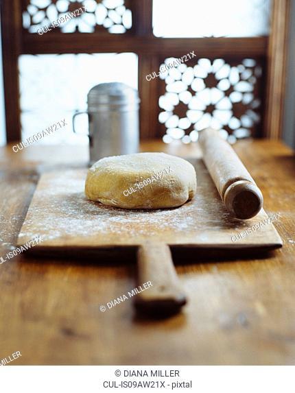 Dough, rolling pin on wooden chopping board, making bread