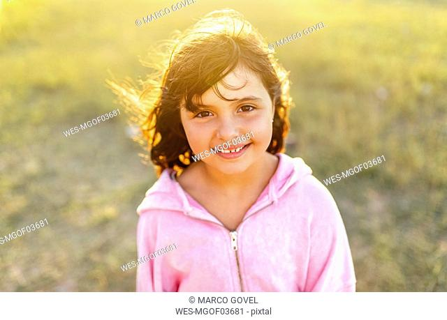 Portrait of smiling little girl with blowing hair at backlight