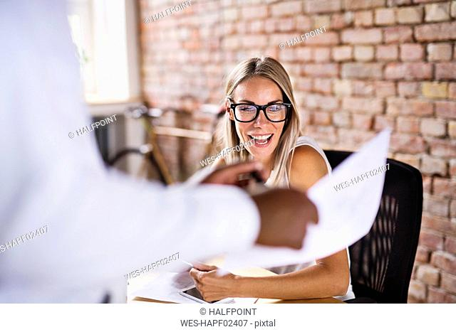 Colleague showing paper to happy woman at desk in office