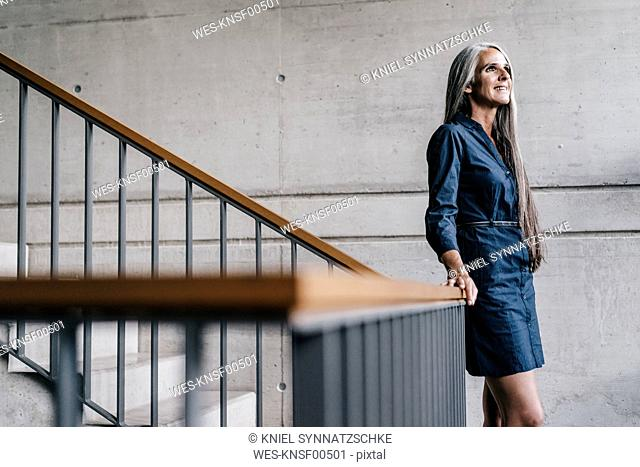 Smiling woman with long grey hair in staircase