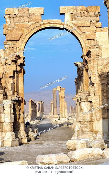 The archeological site of the greco-roman ruins of the city of Palmyra with a giant arch leading to a long, ancient drive way made of stones, at blue sky