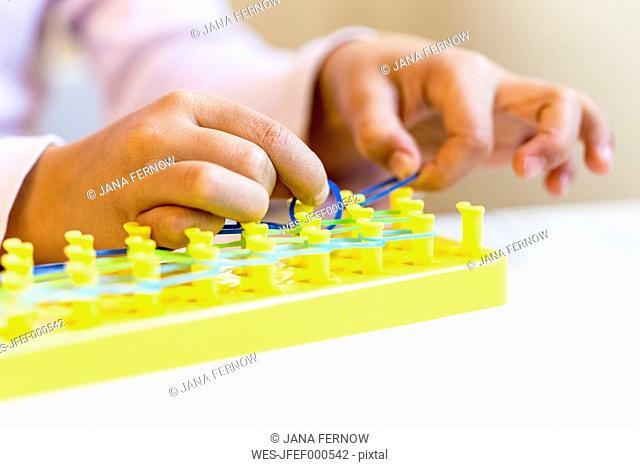 Little girl's hands making bracelets with loomboard