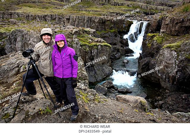 Tourist couple standing at waterfalls; Iceland