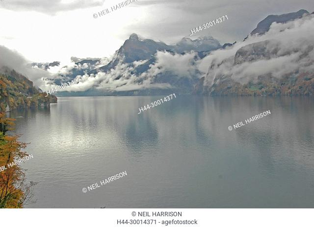Lake surrounded by mountains under a heavy overcast sky in the Fall, Lake Luzern, Switzerland