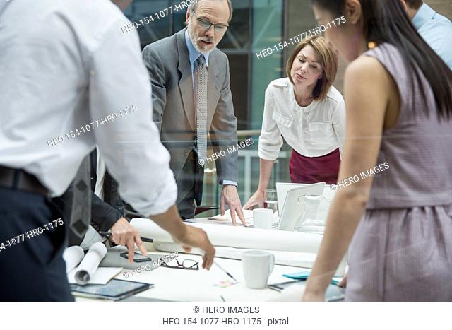Business people reviewing blueprints in conference room meeting