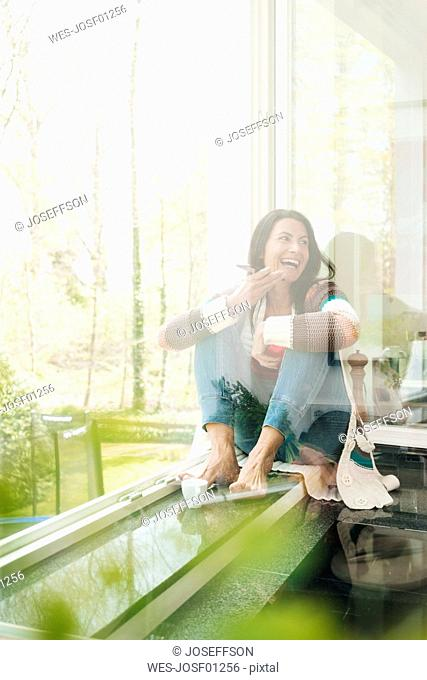 Laughing woman at home sitting on windowsill